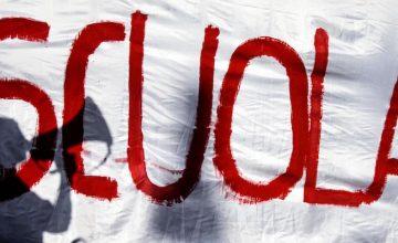 L'ombra di una ragazza con il megafono riflessa su uno striscione con la scritta 'Scuola' durante lo sciopero nazionale della scuola, Roma, 10 ottobre 2014. ANSA/ANGELO CARCONI